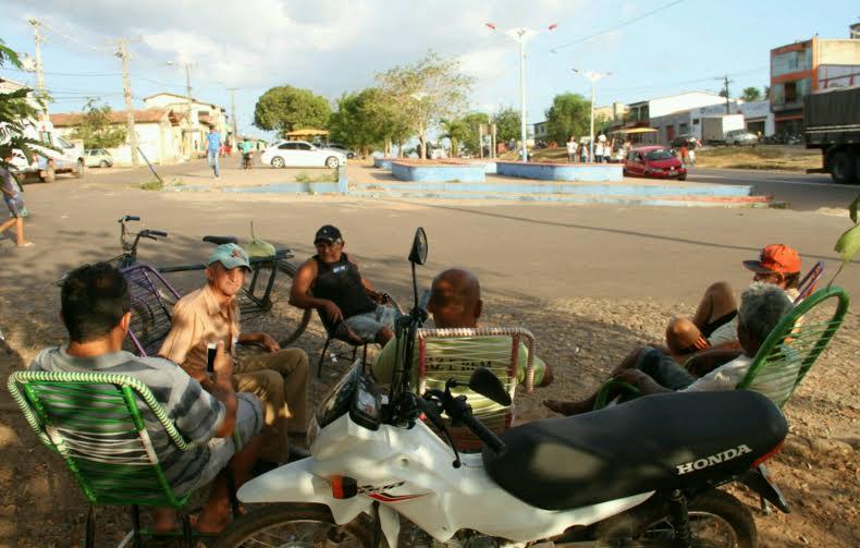 Moradores sentados em praça pública discutem a situação do município / Foto: Biaman Prado